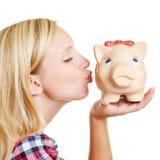 Küssendes Sparschwein der blonden Frau Stockfotografie