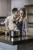 Küssendes und beim Kochen einer Mahlzeit in der Küche flirtendes glückliches Paar Stockbilder
