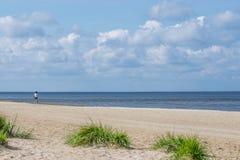 K?ste des Strandes mit einsamem Radfahrer am hellen sonnigen Tag Sonniger heller Tag mit wei?en Wolken lizenzfreies stockbild