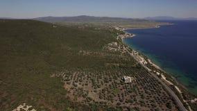 Küste mit Häuschen und grünen Hügeln Vogelperspektive von Trikorfo-Strand, Griechenland stock footage