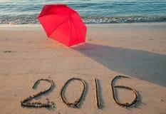 Küste mit Regenschirm und 2016 gezogen auf Sand Stockfotografie