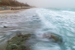 Küste, sandiger Strand, unscharfe Wellen Lizenzfreie Stockbilder