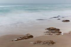 Küste, sandiger Strand, unscharfe Wellen Stockfoto