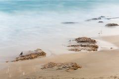 Küste, sandiger Strand, unscharfe Wellen Lizenzfreie Stockfotos