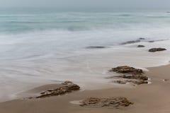 Küste, sandiger Strand, unscharfe Wellen Lizenzfreies Stockbild