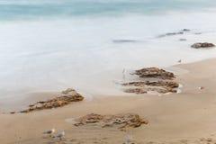 Küste, sandiger Strand, unscharfe Wellen Stockfotografie