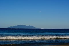 Küsten von Neuseeland; schöner Meerblick, heller blauer Ozean, ein Schiff weit weg und Mond über dem Meer lizenzfreie stockfotografie