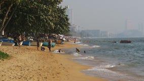Küstenlinie des Strandes Leute baden im Meer, wässern Fahrten, Wellenschlag auf dem sandigen Ufer thailand Pattaya stock video footage