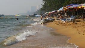 Küstenlinie des Strandes Leute baden im Meer, wässern Fahrten, Wellenschlag auf dem sandigen Ufer thailand Pattaya stock video