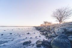 Küstenlinie durch ein gefrorenes Meer im Winter lizenzfreie stockfotos