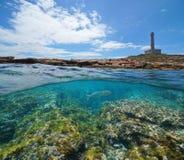 Küstenlinie mit einem Leuchtturm und einem felsigen Meeresgrund mit Fischen unter Wasser stockfoto