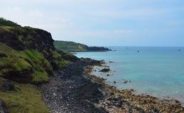 Küstenlinie mit felsigem, blauem Wasser Stockfoto