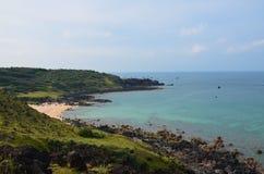 Küstenlinie mit felsigem, blauem Wasser Stockbild