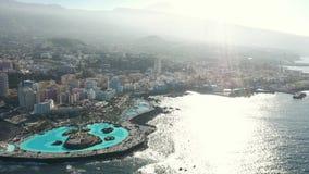 Küstenlinie mit Gebäuden und Hügeln auf der Insel gewaschen durch Ozean stock footage