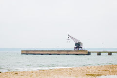 Küstenlinie mit Pier und Kran während des Herbstes Lizenzfreies Stockfoto