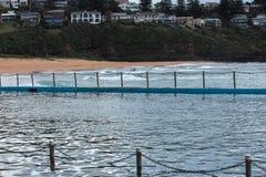 Küstenozean-Swimmingpool mit den Wellen, die auf Strand im Hintergrund rollen Lizenzfreies Stockbild
