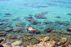 Küstenseeblaues Wasser und -steine Beschaffenheit, Hintergrund für einen Standort, Fahne, Text, Aufkleber Lizenzfreie Stockbilder