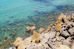 Küstenseeblaues Wasser und -steine Beschaffenheit, Hintergrund für einen Standort, Fahne, Text, Aufkleber Lizenzfreies Stockbild