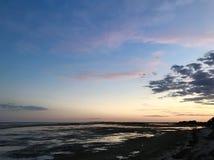 Küstenvorland bei Sonnenuntergang mit Felsen und Meerespflanze Orange Reflexionen stockfoto