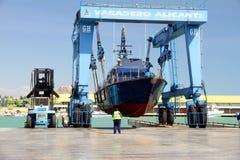 Küstenwache der spanischen Gewohnheiten über einem travelift vor gehen zum Wasser lizenzfreies stockbild