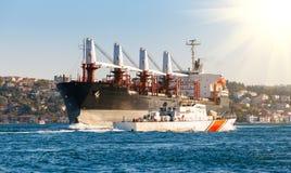 Küstenwacheschiff und großes Frachtschiff, die entlang dem Bosphorus-Kanal fortfahren lizenzfreie stockbilder