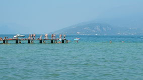 Kąpielowicze ma zabawę na molu przy Gard jeziorem zbiory