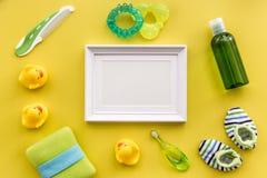 Kąpielowy kosmetyczny ustawiający dla dzieciaków, ramy, ręcznika i zabawek tła odgórnego widoku żółtej przestrzeni dla teksta, Fotografia Stock