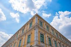 Kąta żółty budynek na niebieskim niebie z chmurą Zdjęcia Stock