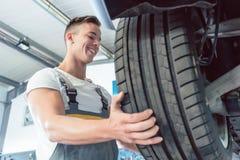 Kąta widok ręka wykwalifikowany auto mechanik trzyma oponę Obraz Royalty Free