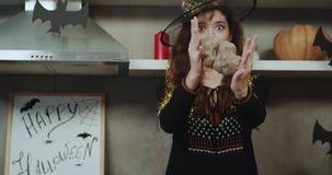Kędzierzawa Azjatycka dama maskująca w czarownicie ono uśmiecha się przed kamerą śmiesznymi z niektóre dla Halloweenowego zbliżen zbiory wideo