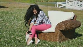Kędzierzawa brunetka relaksuje w łozinowym karle na zielonej trawie i uderzeniach kot zdjęcie wideo