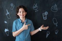 Kędzierzawa chłopiec uśmiecha się lody i oferuje zimnych napoje i obrazy royalty free