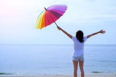 Kędzierzawa dziewczyna przy morzem tła odosobneni parasolowi białej kobiety potomstwa obraz stock