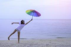 Kędzierzawa dziewczyna przy morzem tła odosobneni parasolowi białej kobiety potomstwa zdjęcie stock