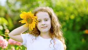 Kędzierzawa dziewczyna w białej koszulce jest uśmiechnięta, trzyma słonecznika w parku w lecie zbiory wideo