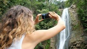 Kędzierzawa kobieta nakłania ostrość na telefonu ekranie i fotografuje siklawę w parku zbiory