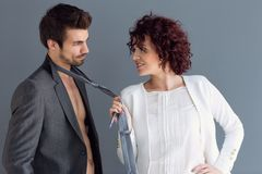 Kędzierzawa kobieta pozuje z mężczyzną wlec jego krawat obrazy stock