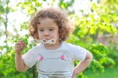 Kędzierzawa mała dziewczynka dmucha mydlanych bąble Zdjęcia Stock