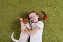 Kędzierzawa małej dziewczynki obejmowania szczeniaka dźwigarka Russell zdjęcia royalty free