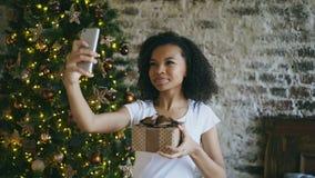 Kędzierzawa nastoletnia dziewczyna gawędzi online rozmowę używać smartphone kamerę w domu blisko choinki zbiory wideo