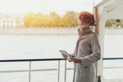 Kędzierzawa zadumana dziewczyna z cyfrową pastylką na statku pokładzie Obraz Royalty Free