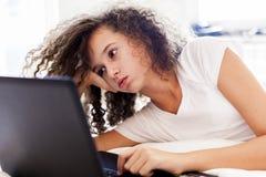 Kędzierzawego włosy nastoletniego gitl websurfing internet na laptopie zdjęcie royalty free