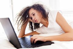 Kędzierzawego włosy nastoletniego gitl websurfing internet na laptopie zdjęcie stock