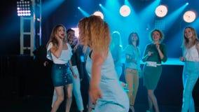 Kędzierzawy dziewczyna taniec przy partyjnym noc klubem Wesoło przyjaciele firma Dyskoteka w błękitnych brzmieniach, nowożytny mł zbiory