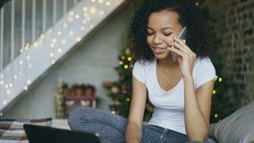 Kędzierzawy mieszany biegowy dziewczyny gawędzenia smartphone i używać w domu laptop na choinki backround zbiory