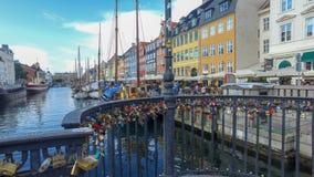 Kędziorki na moście przy Nyhavn z łodziami i barwionymi budynkami w tle fotografia stock