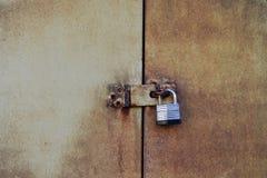 Kłódka na rdzewiejącym metalu drzwi obraz stock