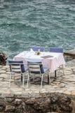 Kłaść krzesła przy restauracją morzem i stół Obraz Royalty Free