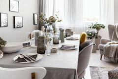 Kłaść stół z talerzami i szkłami w popielatym jadalni wnętrzu Istna fotografia obrazy stock