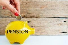 Kładzenie pieniądze w żółtym prosiątko banku dla emerytura, ubezpieczenia społecznego pojęcie Fotografia Royalty Free